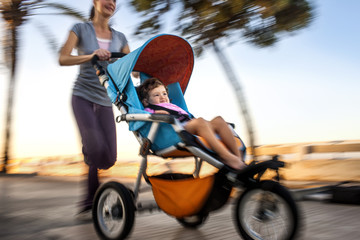 Woman jogging while pushing her daughter in a stroller.