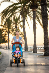 Mother pushing her daughter in a stroller along the waterfront.
