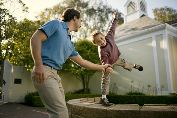 Happy mid adult man helping his son to balance on a stone wall.