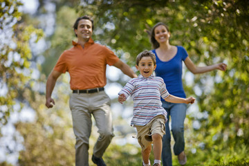 Laughing parents running after their happy young son in a park.