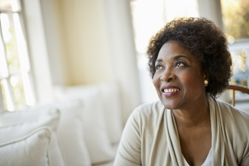 Smiling middle aged woman sitting in her living room.