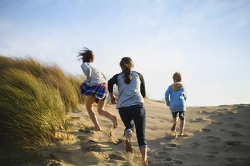 Three children run up a grassy sand dune.