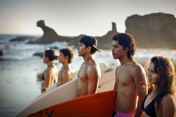 Teenagers standing on the beach in a row carrying surfboards, El Salvador.