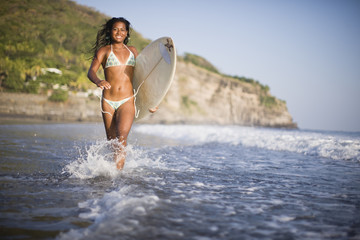 Girl carrying surfboard and running on the beach, El Salvador.