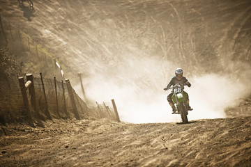 Motorbike racer racing through a dirt road.