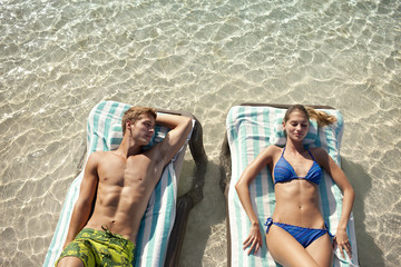 Young couple lying down on deck chairs in shallow water.