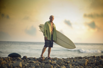 Male surfer holding his board as he poses for a portrait front of the sea.