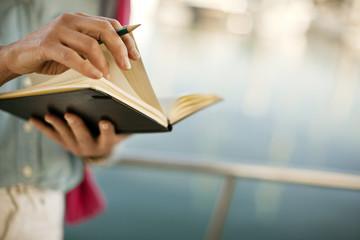 Woman flicks through a diary.
