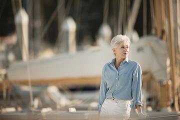 Senior woman wearing chambray shirt stands looking out at a marina.