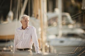 Senior man poses for a portrait at a marina.