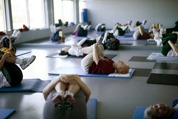 Elderly exercise class stretches on mat.