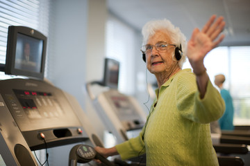 Elderly woman with headphones on treadmill waves.