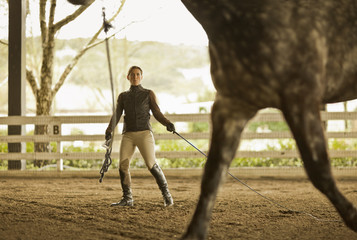 Mid adult woman training her horse in an exercise yard.