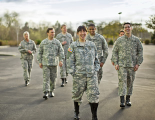 Group of US Army soldiers smile and laugh together as they walk across a parking lot after a training exercise.