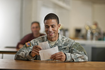 US Army soldier smiles happily as he opens his letters from home.