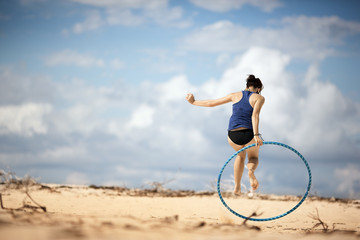 Young woman using a hula hoop at the beach.