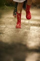 Red gumboots splashing through a rain puddle.