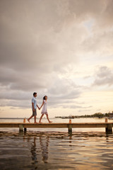 Happy mid adult couple walking hand in hand along a pier.