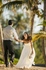 Radiant bride grinning at her new husband as they have fun together on the beach.
