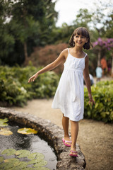 Smiling young girl having fun balancing on the stone wall of a garden fishpond.
