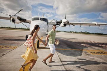 Smiling young married couple walking hand in hand toward an airplane.