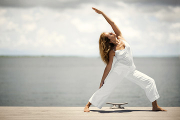 Relaxed middle-aged woman doing yoga stretches on the end of a wooden jetty.