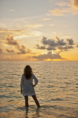 Young woman standing ankle deep in the tropical ocean while watching the beautiful sunset.