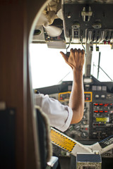 Pilot pulls a handle in the cockpit of an airplane.
