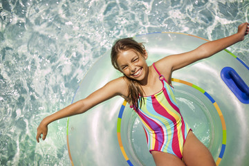 Portrait of a laughing girl sitting on an inflatable ring in a swimming pool.