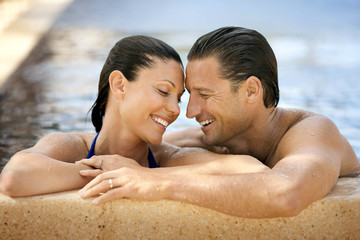 Happy mid-adult couple smiling while standing close to each other in a swimming pool.