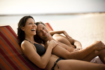 Happy mid-adult couple laughing while lying side by side on a deck chair at a beach resort.