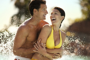 Smiling couple embracing in a swimming pool.