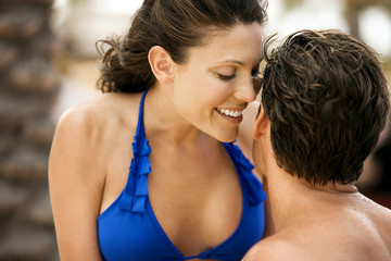 Smiling mid-adult woman whispering close to her boyfriends ear while in the water at the edge of a swimming pool.