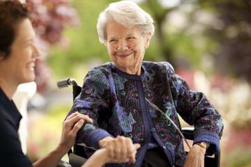 An elderly woman wearing oxygen tubes shares a joke with her daughter.