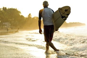 Man walks through the surf carrying a surfboard under his arm as the sun rises ahead of him.