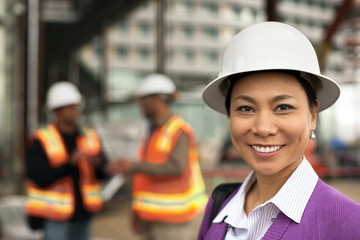 Portrait of smiling middle-aged female architect visiting a construction site.