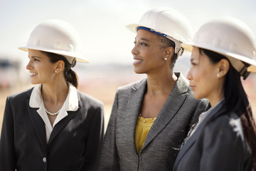 Three smiling female colleagues wearing business suits and hardhats