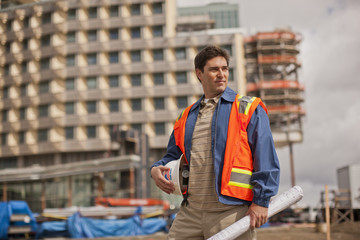 Handsome young architect in a high visibility vest holds his hardhat and building plans on a construction site.