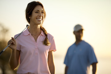 Happy young couple playing golf together.
