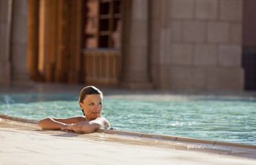Content mid adult woman relaxing in a swimming pool.