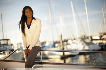 Portrait of young woman standing on the deck of a sailboat.
