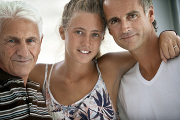Senior man,  his granddaughter and son pose for a portrait together.