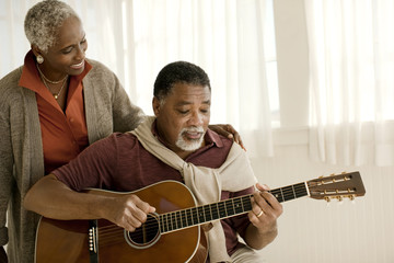 Smiling senior woman listening to her husband play an acoustic guitar.