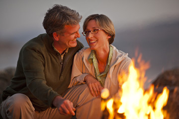 Smiling middle aged couple sitting by a bonfire on a beach.