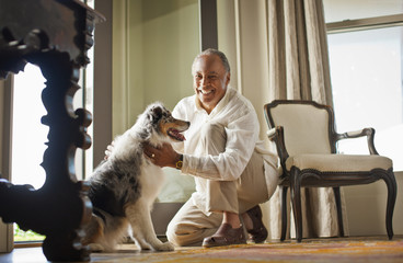 Portrait of a smiling mature man petting his dog.