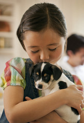 Young girl holding a puppy.