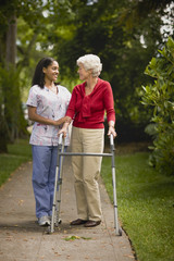 Young nurse assists senior woman with a walking frame.