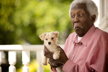Senior man makes a face as he holds a puppy in his hands as he stands on a porch.