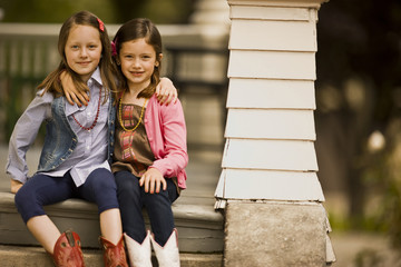 Two young girls with their arms around each other sit together on the top step of porch stairs and smile as they pose for a portrait.