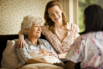 Young woman sits on the edge of a bed and puts a reassuring arm around a senior woman.